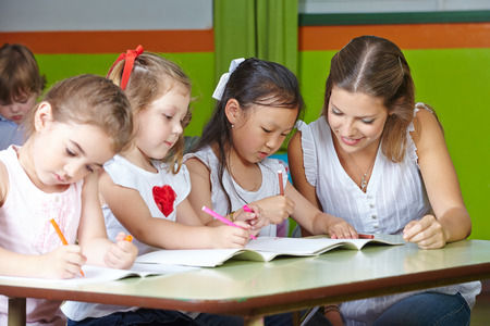 kids at daycare writing with help from teacher