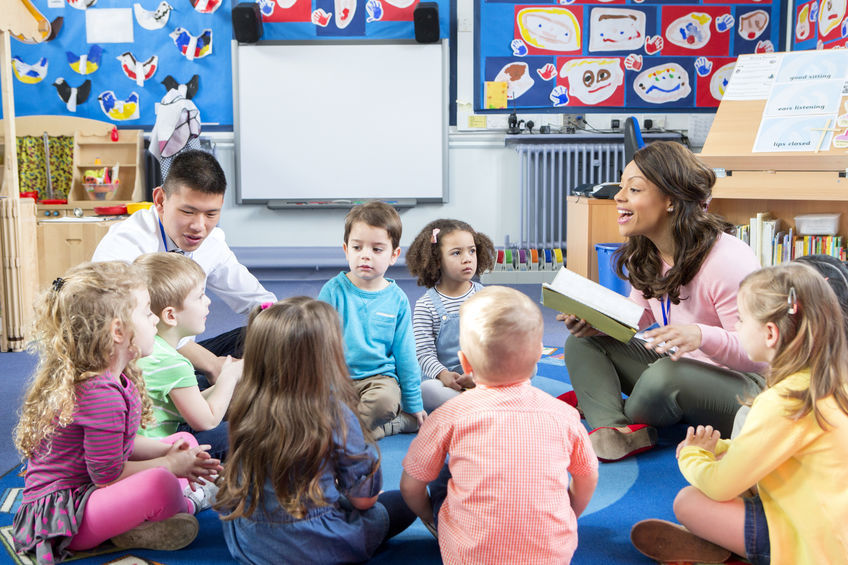 bunch of children in daycare being read a book