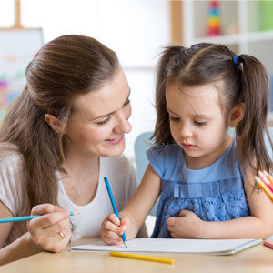 Child drawing with daycare teacher